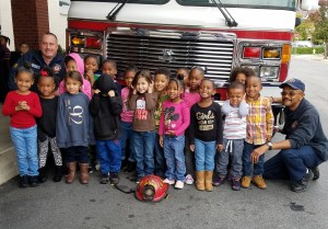 Pre-K Counts poses in front of the fire engine with firefighters Maxfield and Spangler.